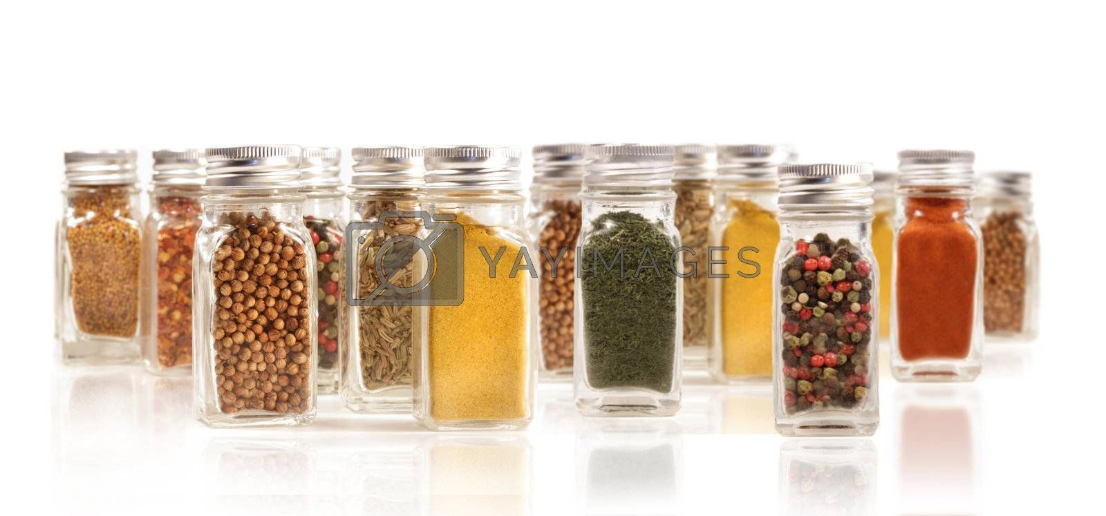 Assorted spice bottles isolated on white background