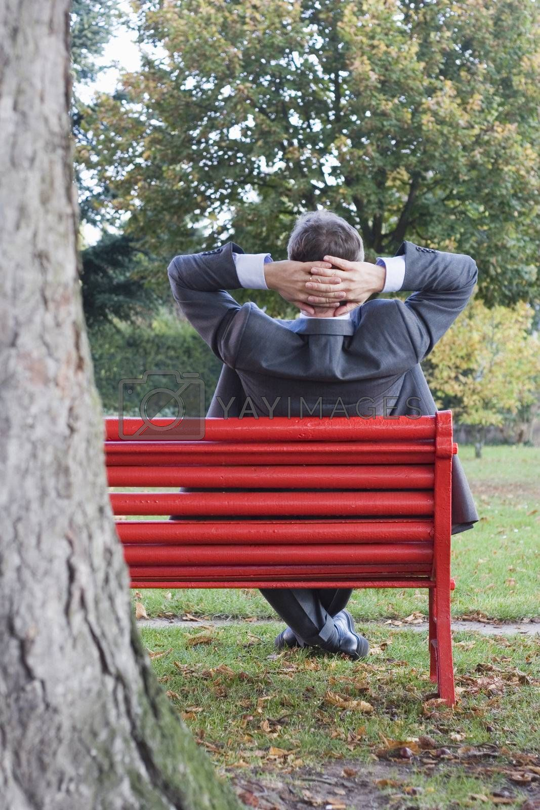 Businessman relaxing on a red park bench