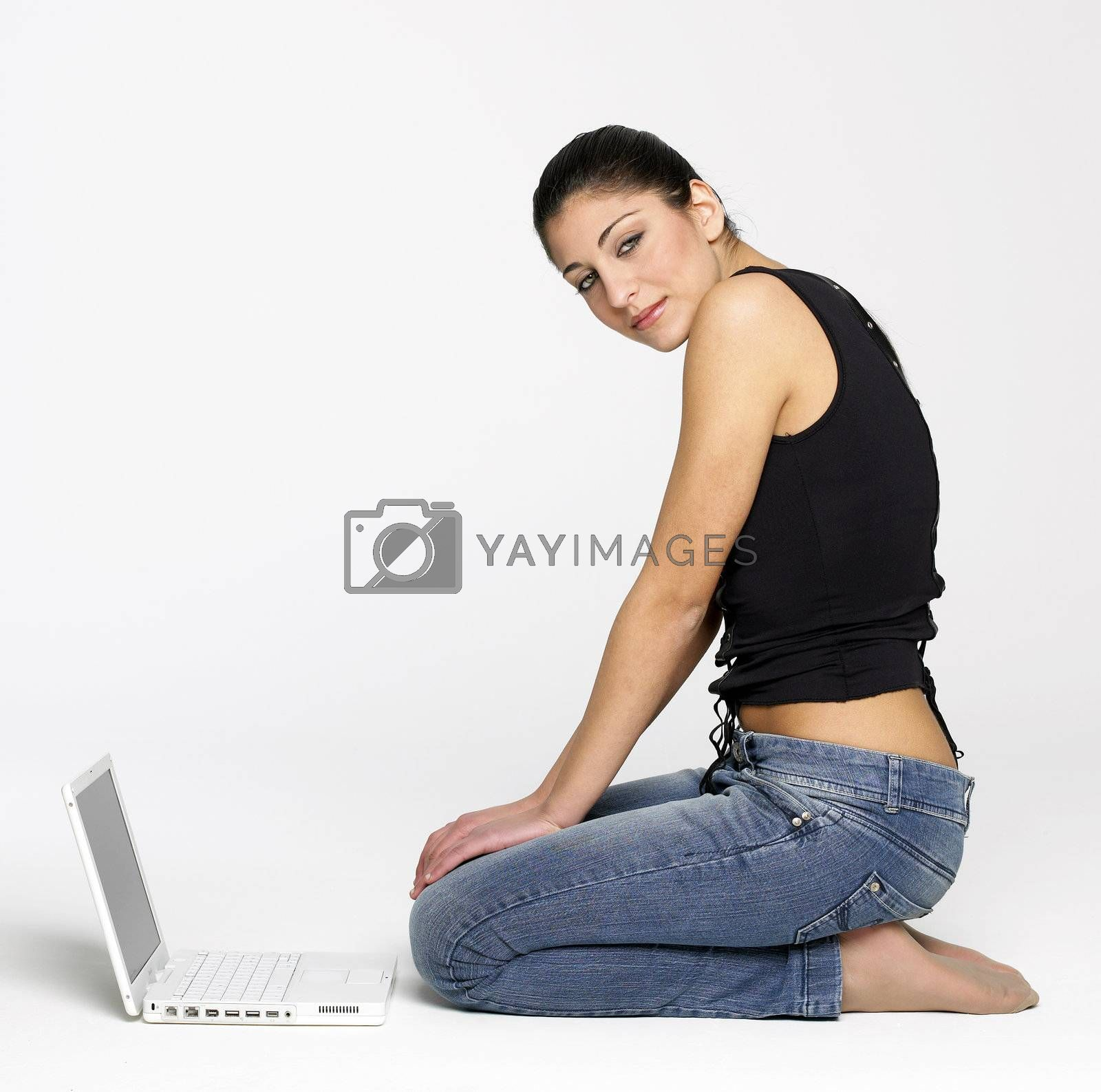 Pretty young girl sitting on floor with laptop