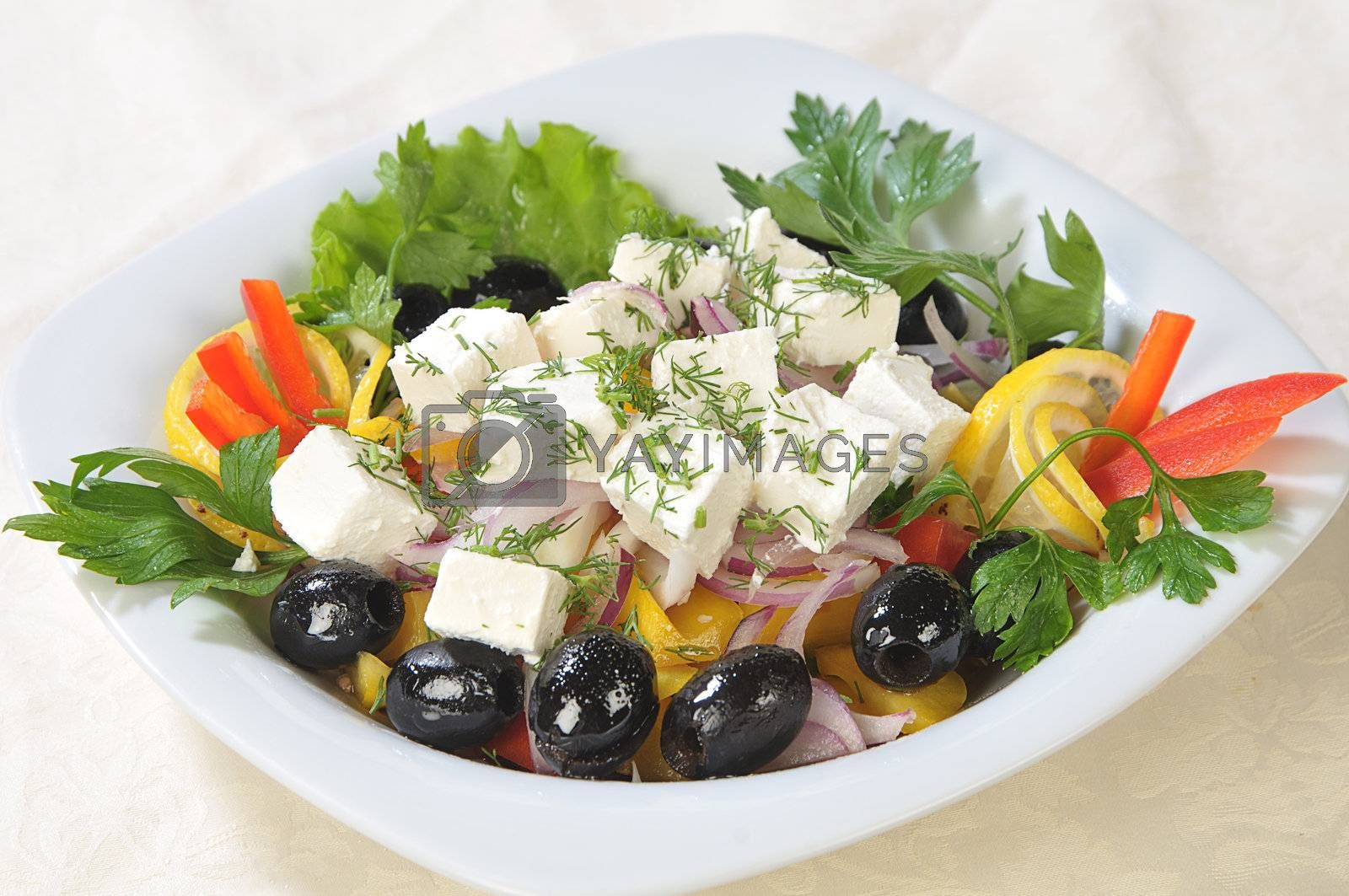Slices of cheese in a salad of feta cheese and diced vegetables