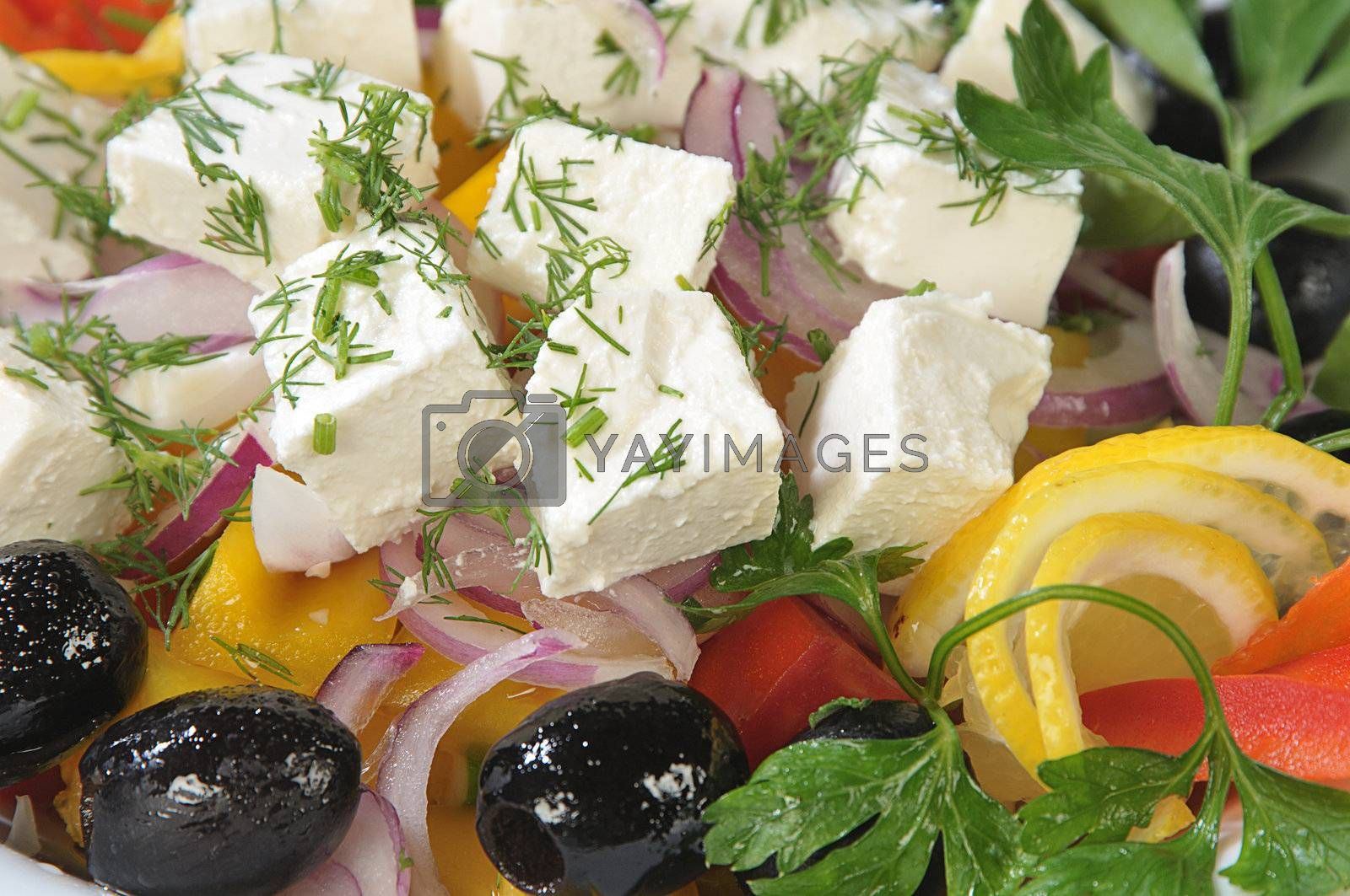 Close-up slices of cheese in a salad of feta cheese and diced vegetables