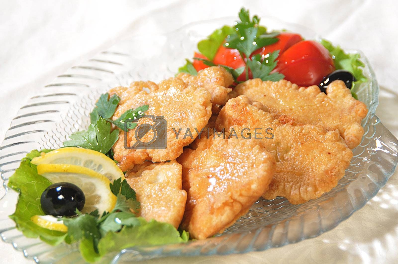 Pieces of fish filet are fried in an egg and decorated a tomato, greenery and olives