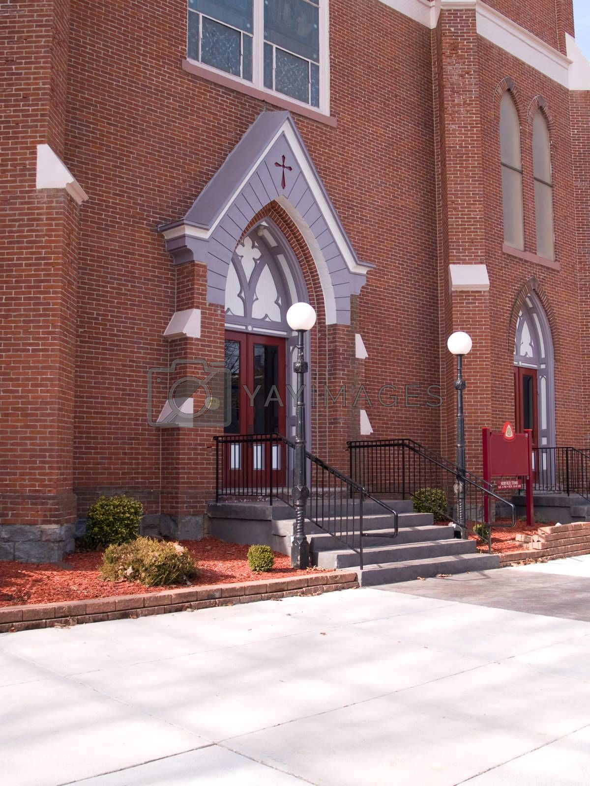 the front of a red brick church with a sidewalk