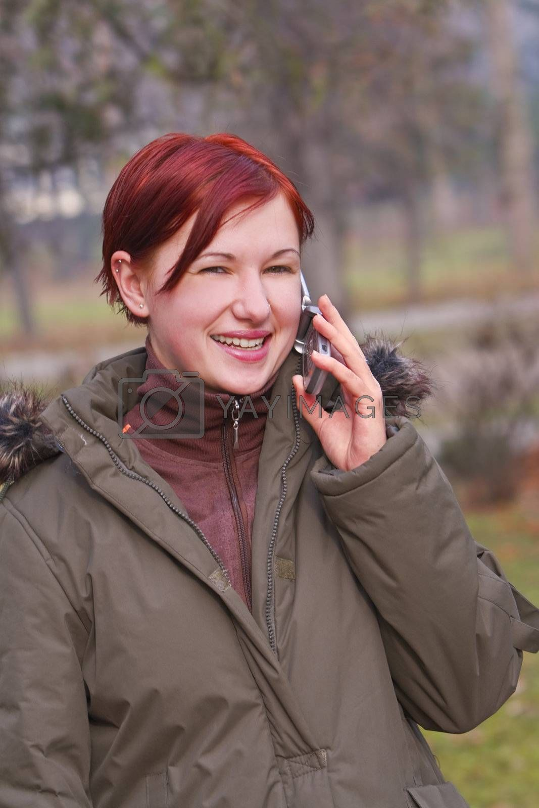 Smiling redheaded girl using a mobile phone in a park.Shot with Canon 70-200mm f/2.8L IS USM