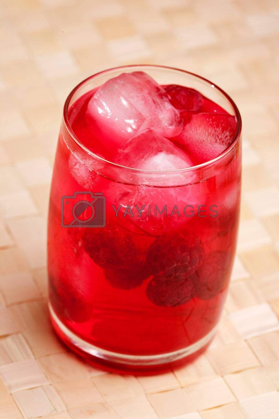 A glass of sparkling raspberry punch outdoors in a natural setting