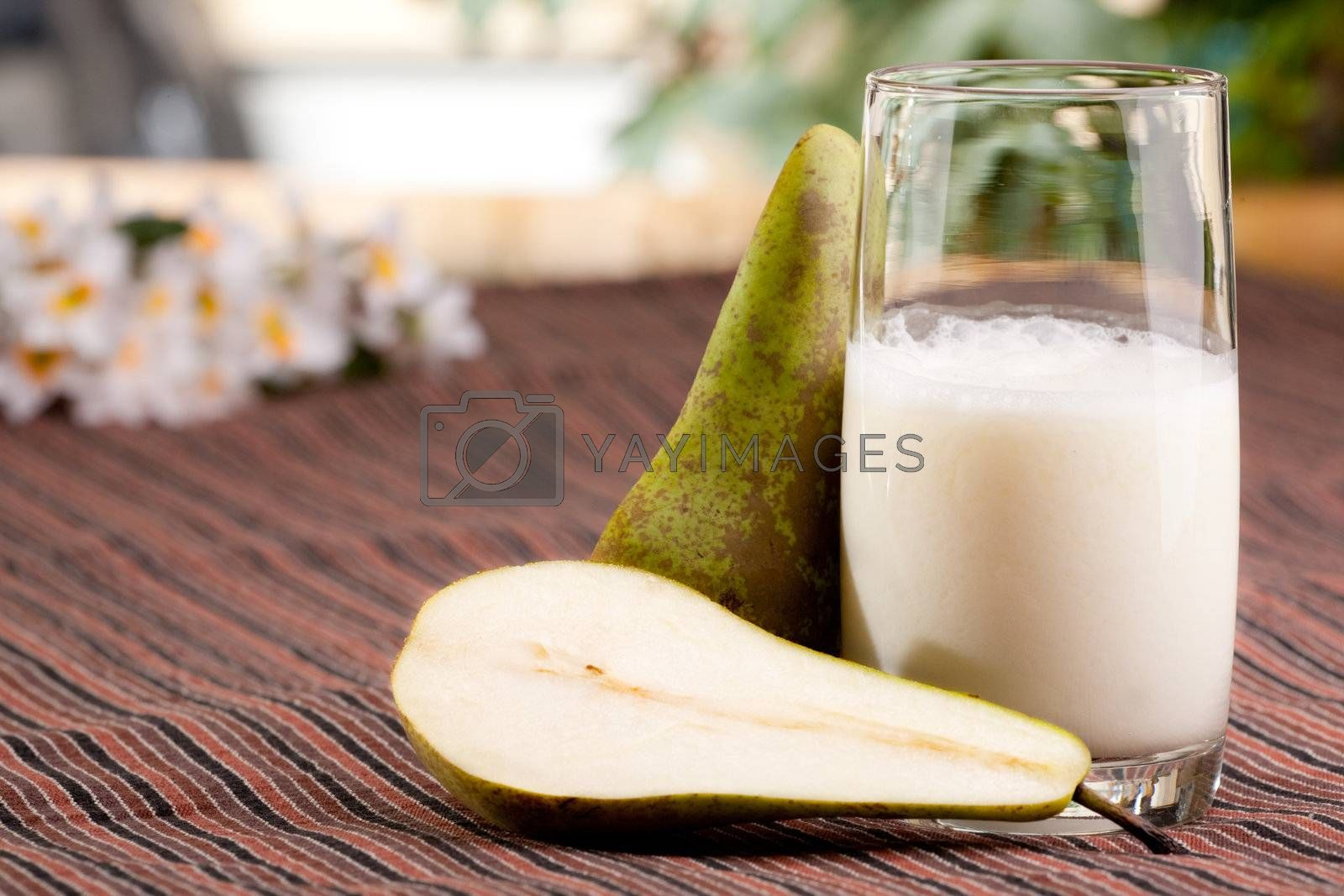 A tall glass of pear smoothie in a natural setting
