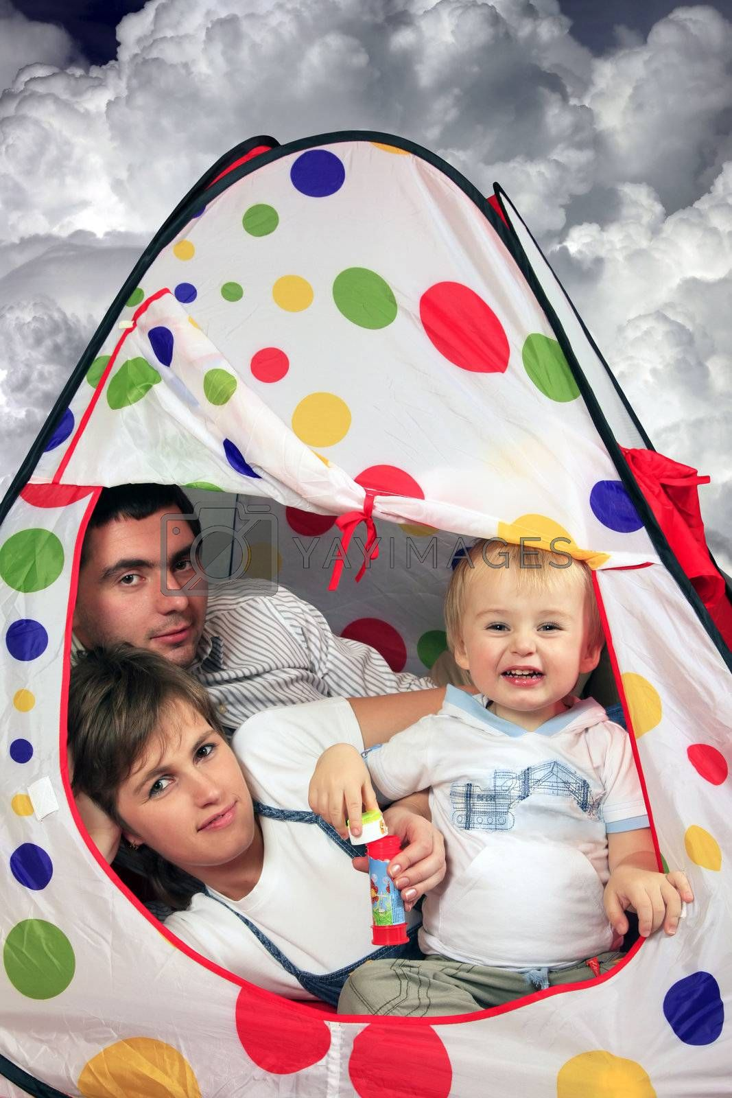 Happy young family with the son in a small house on a background of clouds