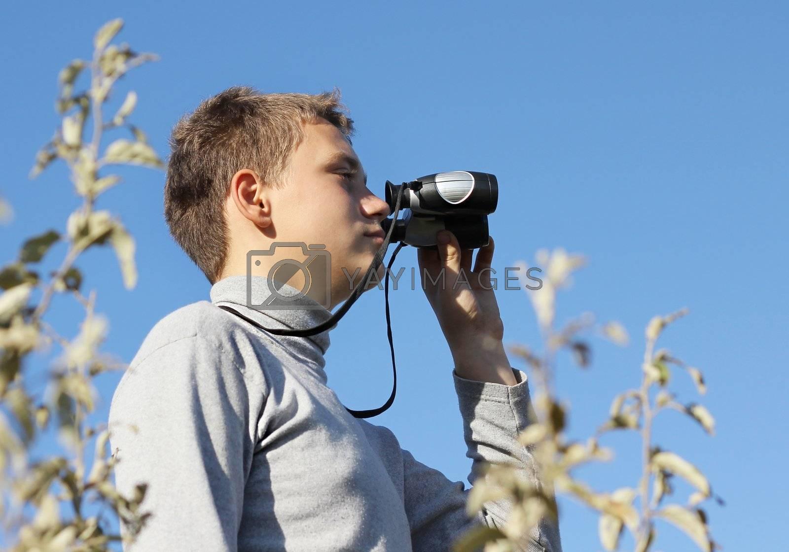 Boy with binoculars in hand in summer day