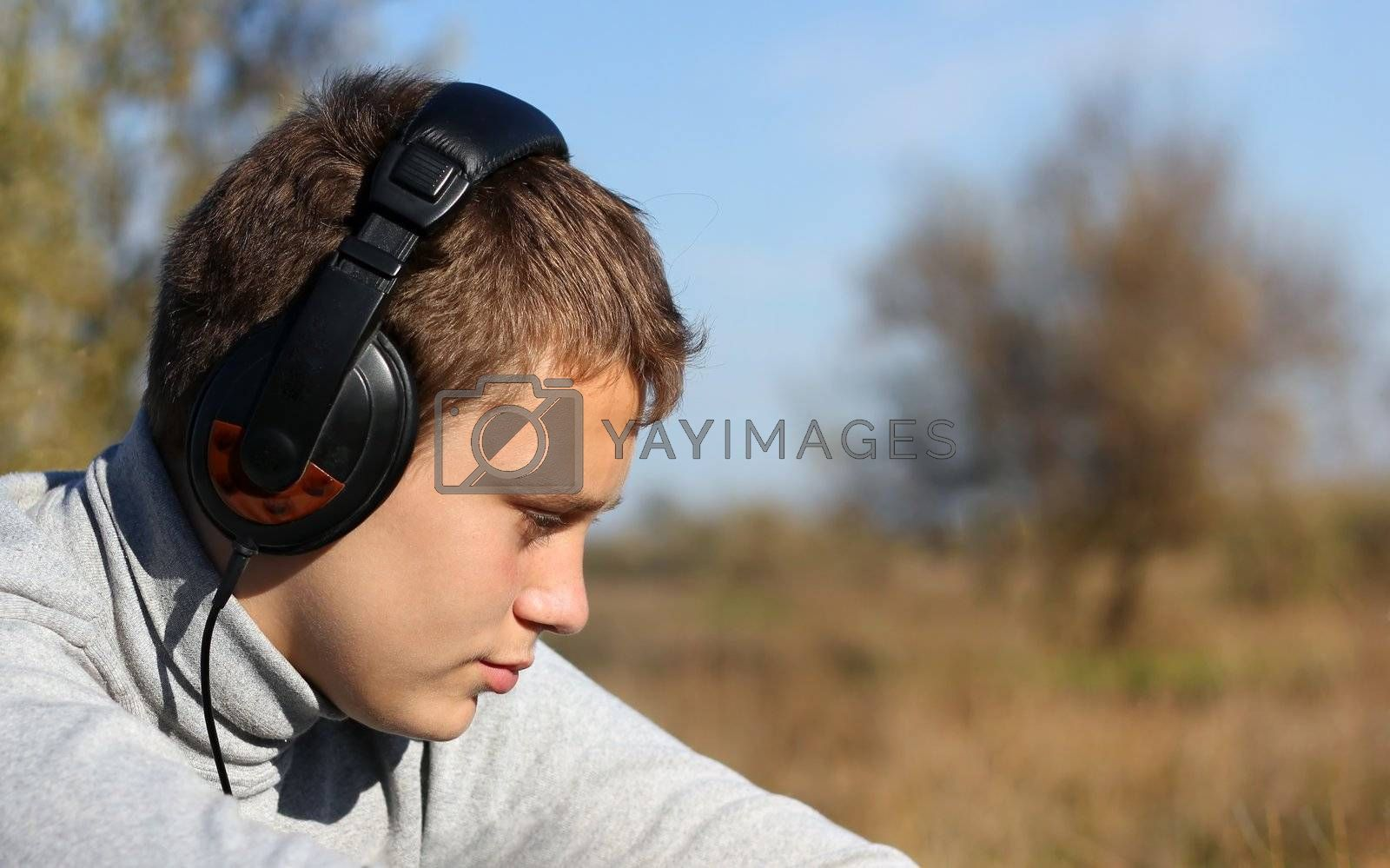 Boy Enjoying Music in headphones in autumn day