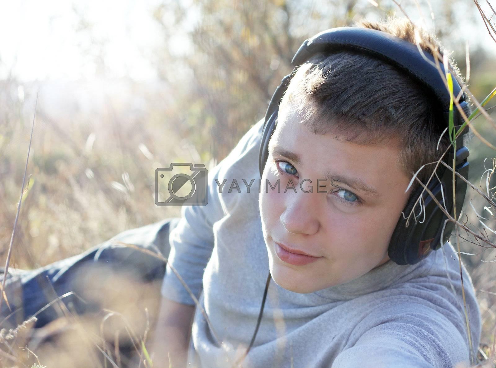 Boy Enjoying Music in autumn day in headphones