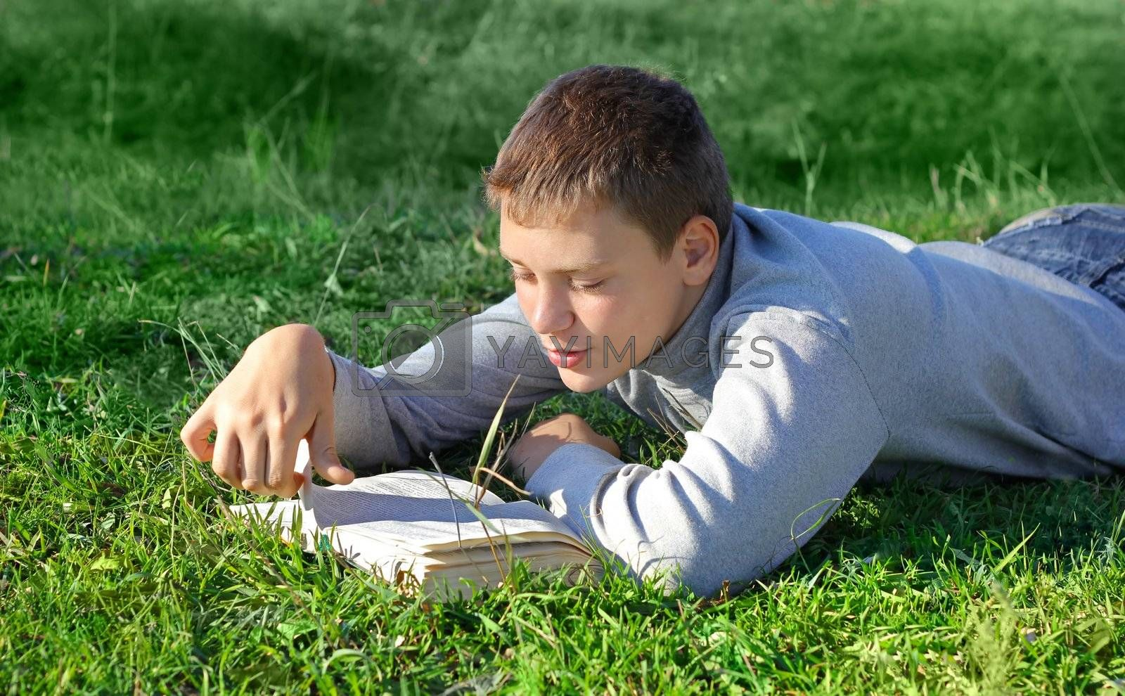 boy with a book on green grass