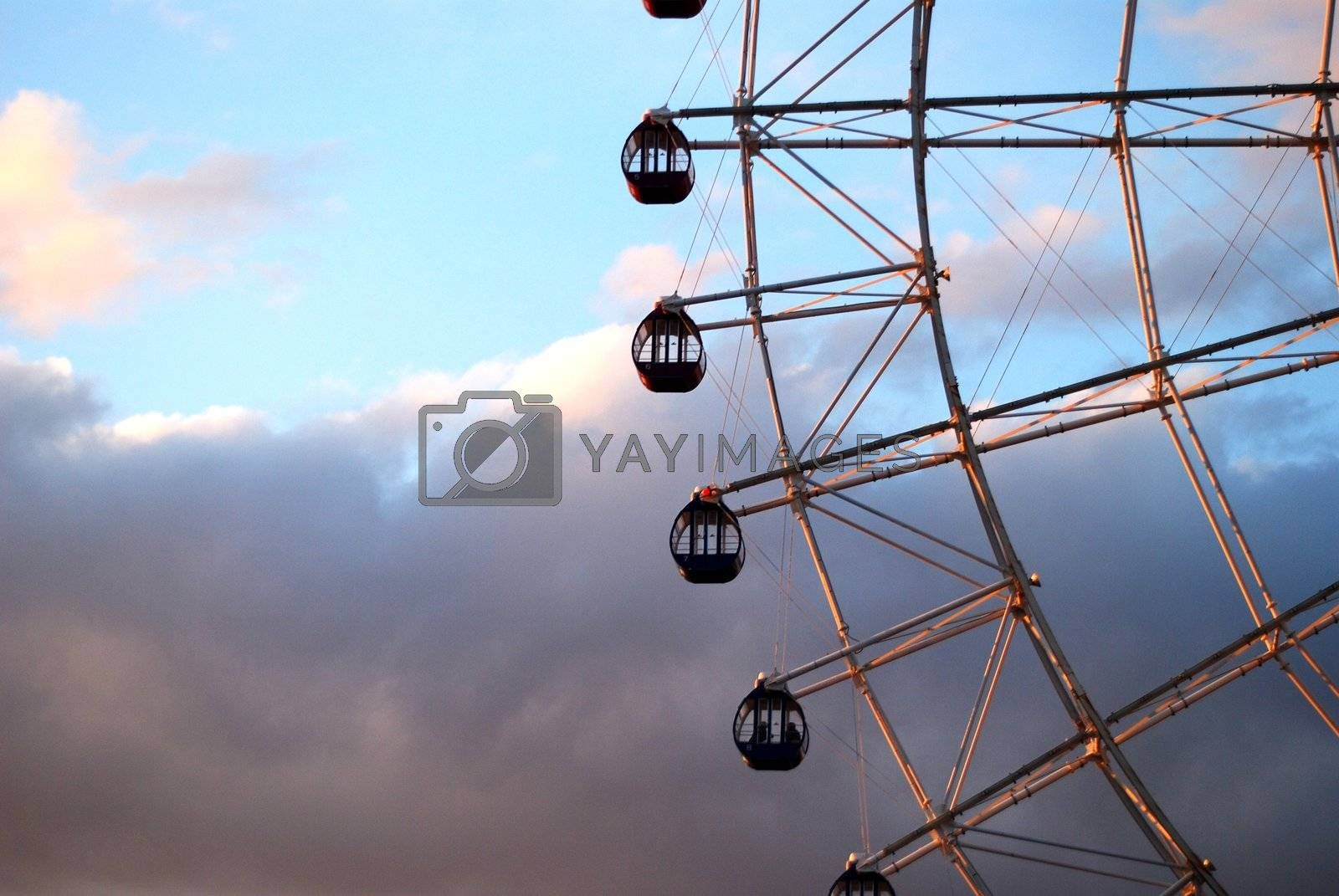section of ferris wheel with four dark blue gondolas against moody sky