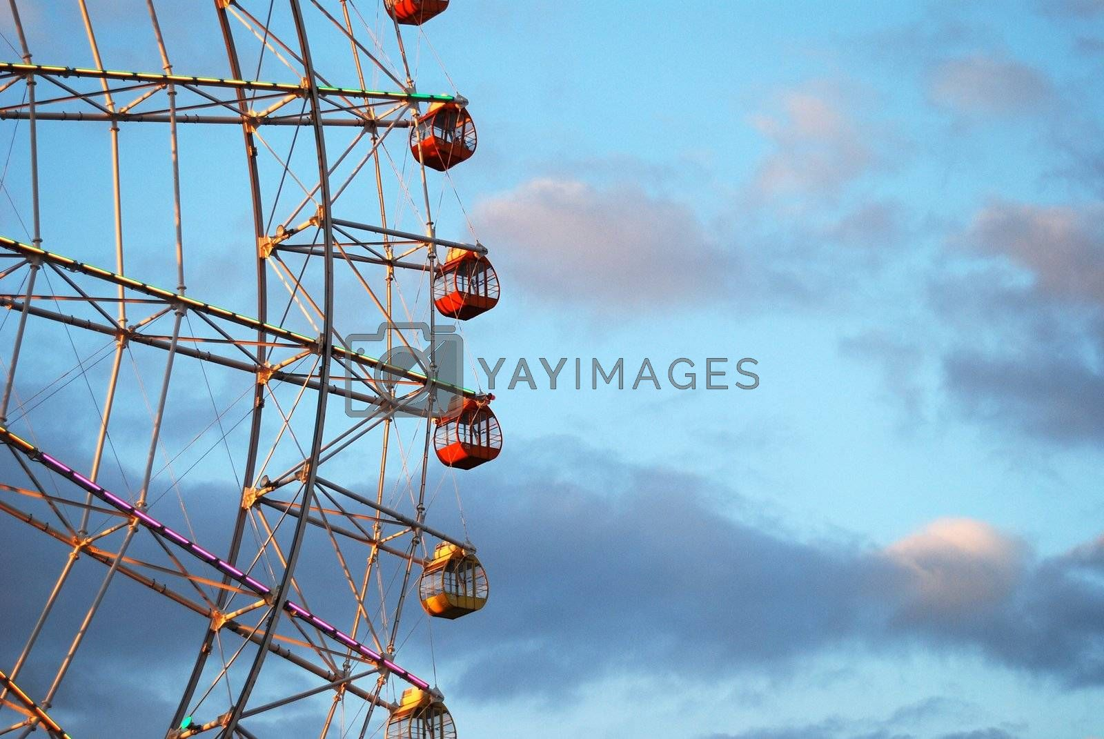 Section of ferris wheel against blue cloudy sky