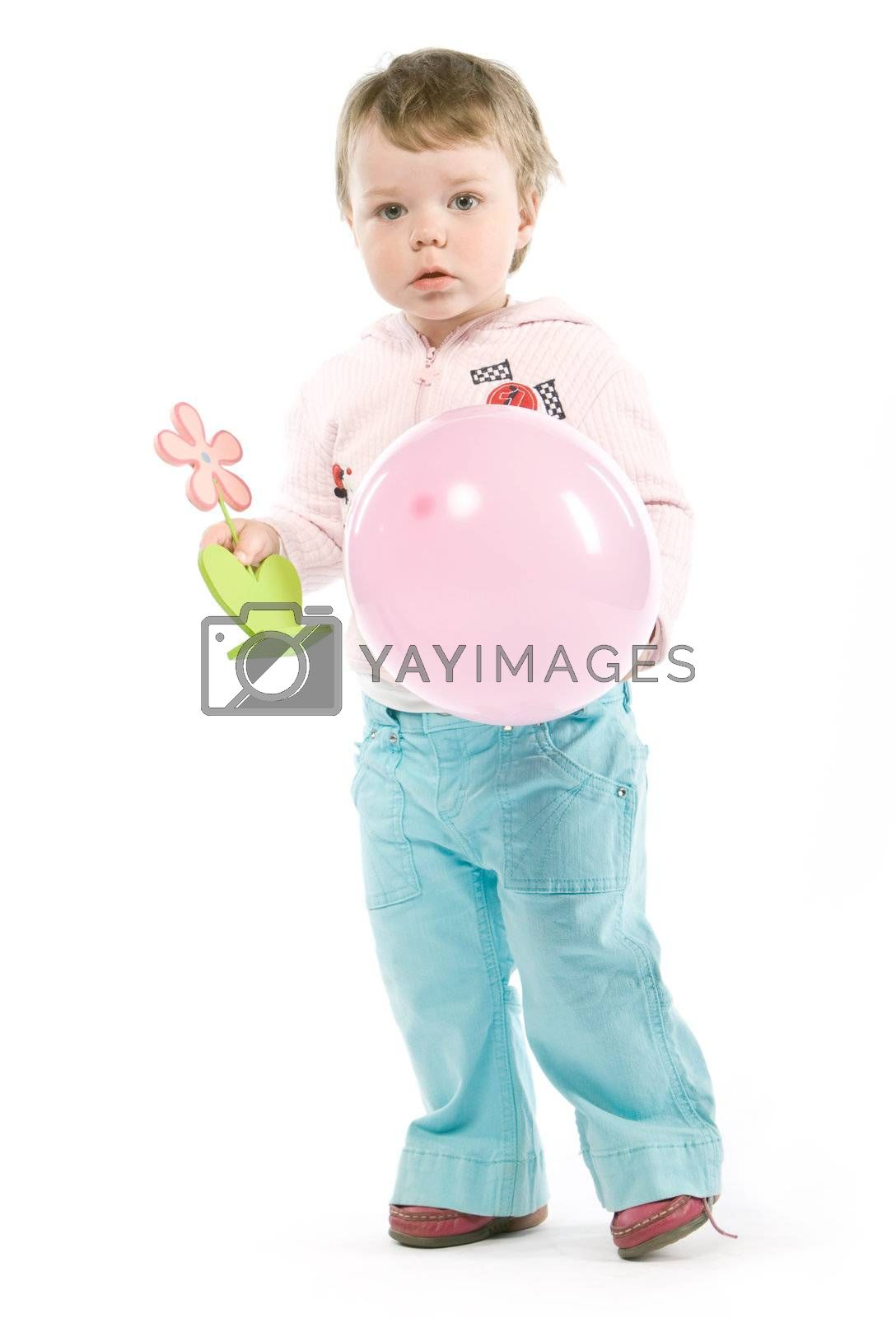 Child with pink jacket, pink balloon, wooden flower. Isolated on white