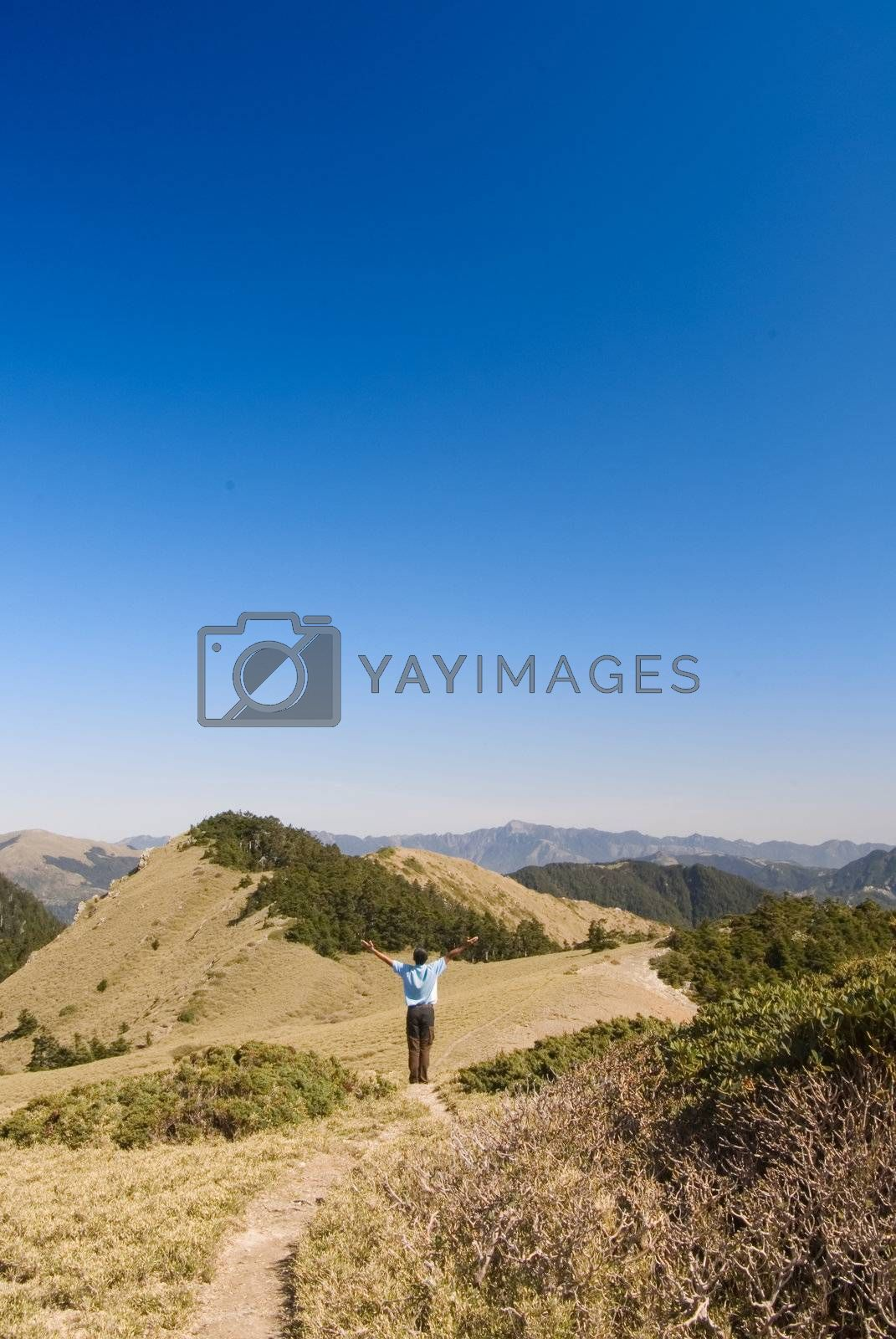 A man stand in the beautiful yellow grassland and blue sky outdoor.