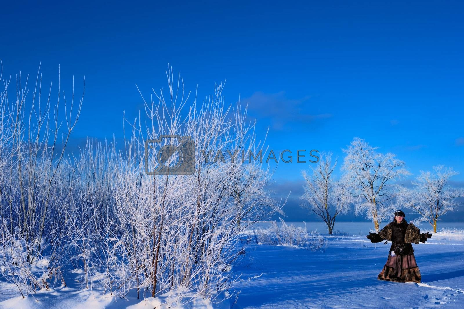 A woman stands in the middle of a snowy field