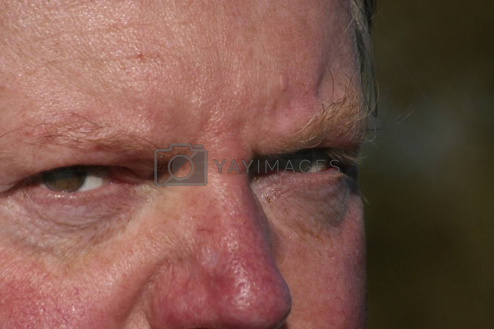 middle aged mans eyes with a angry look in them