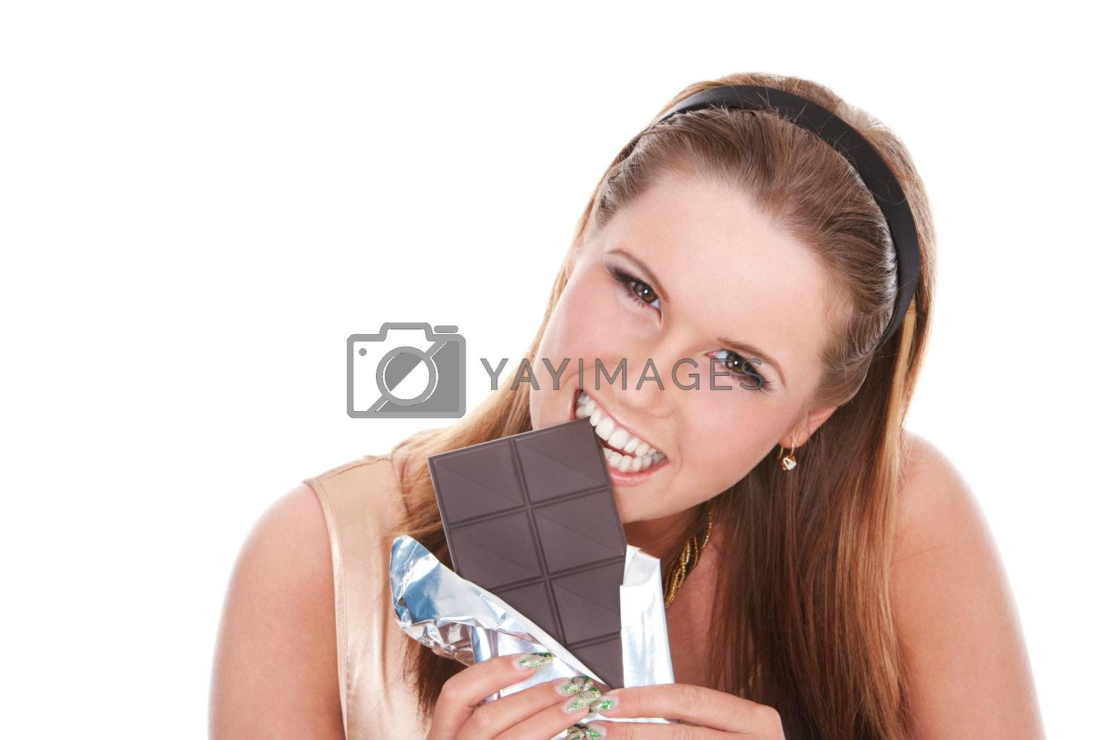 young girl biting a bar of dark chocolate on isolated white