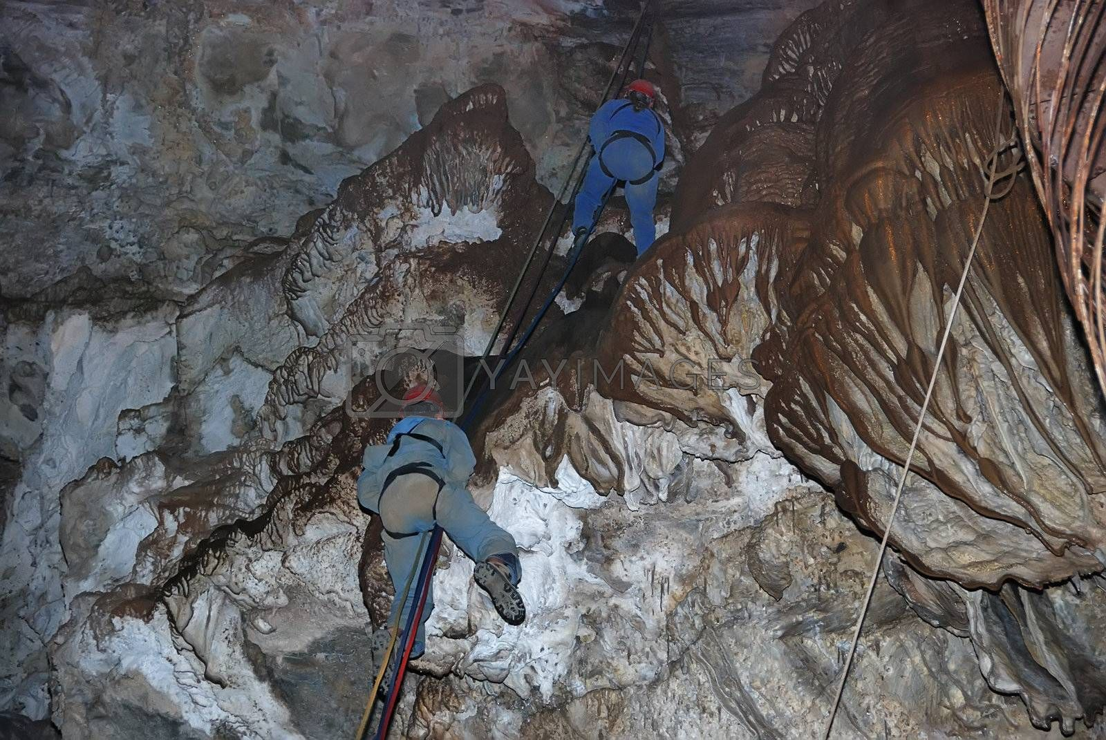 Two climbers on a rope in a cavern.