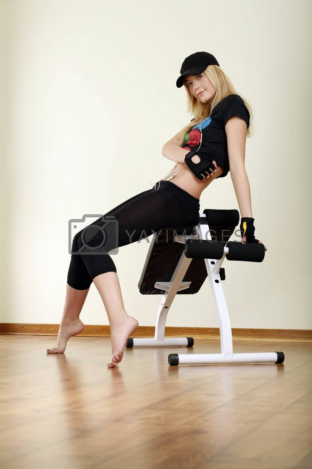 girl in cap sitting on fitness machine
