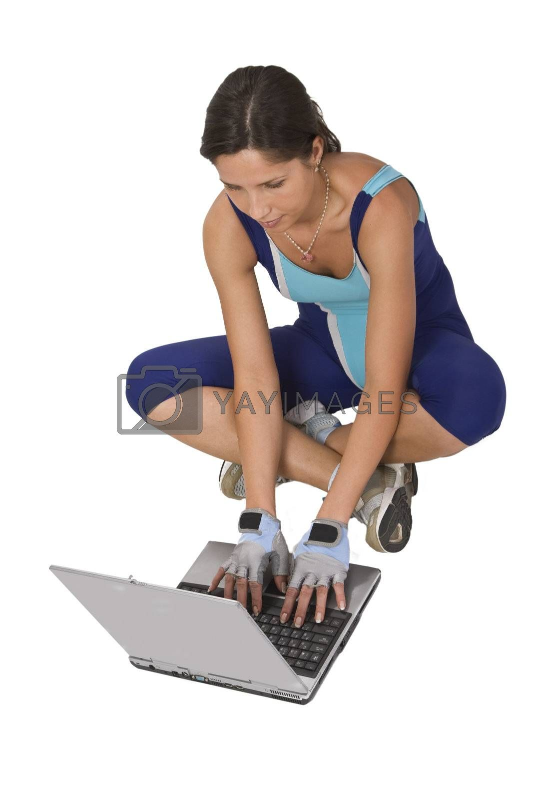Woman in training equipment searching for something on a laptop.
