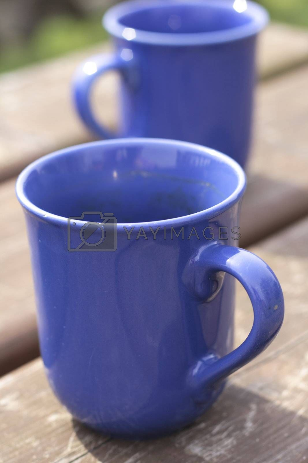 two blue empty ceramic beakers on a wooden table