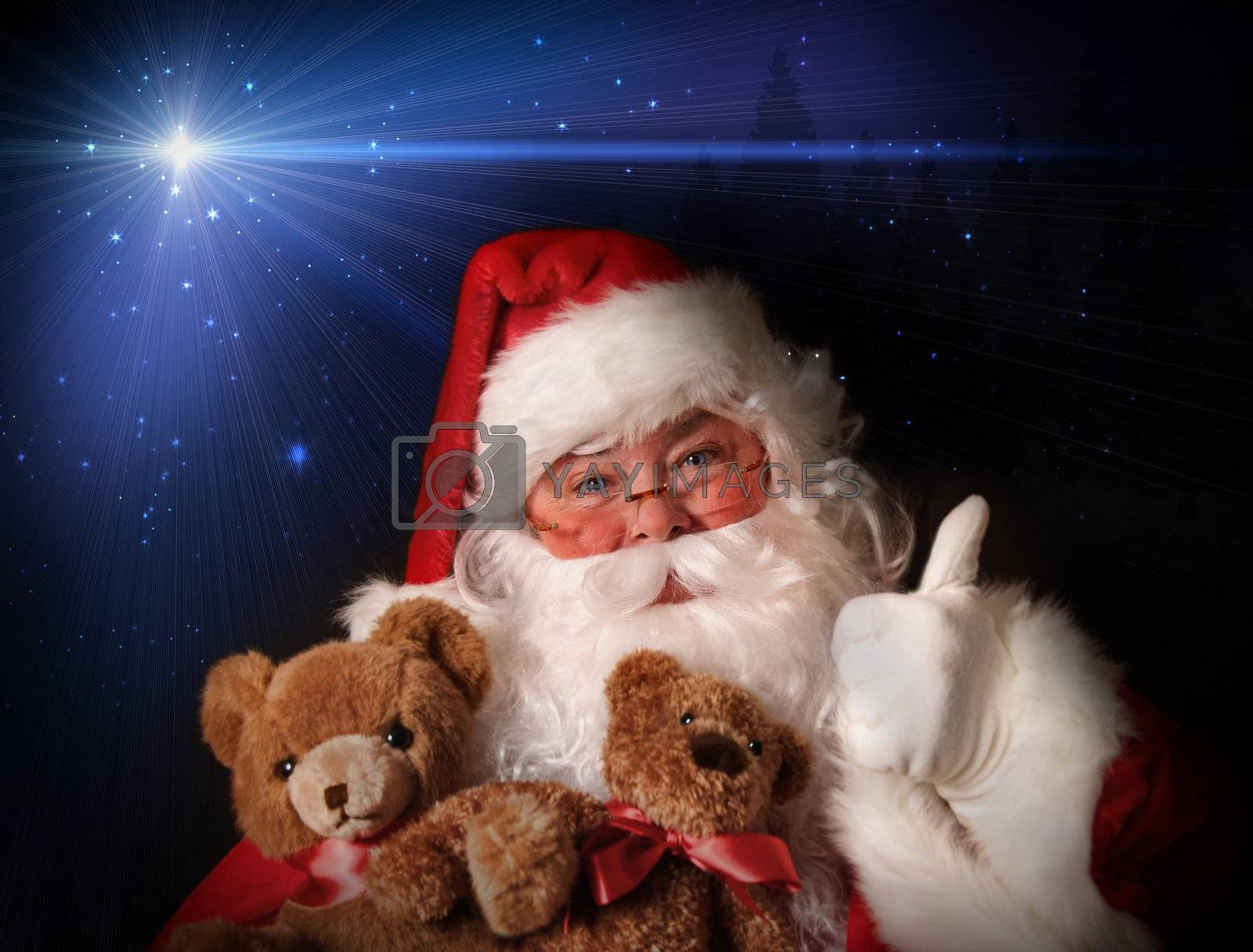 Santa smiling holding toy teddy bears in his arms aginst a night sky