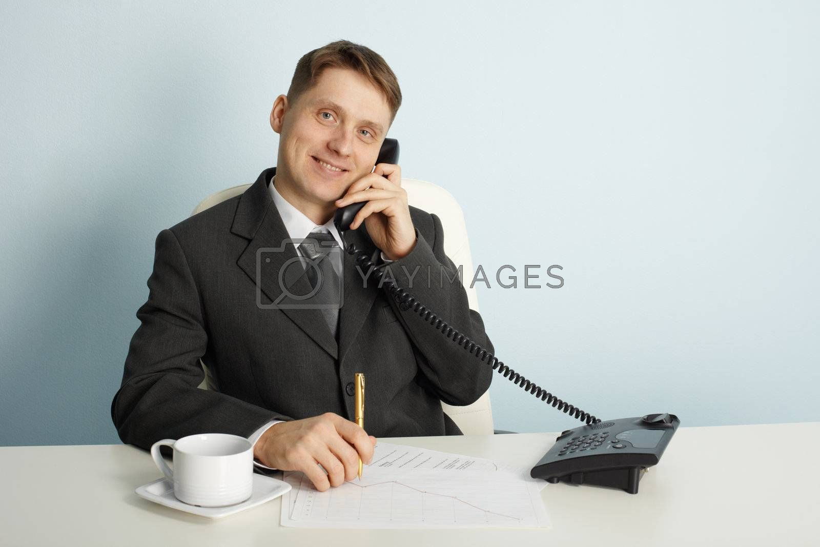 Royalty free image of Smiling businessman in talks on phone by pzaxe