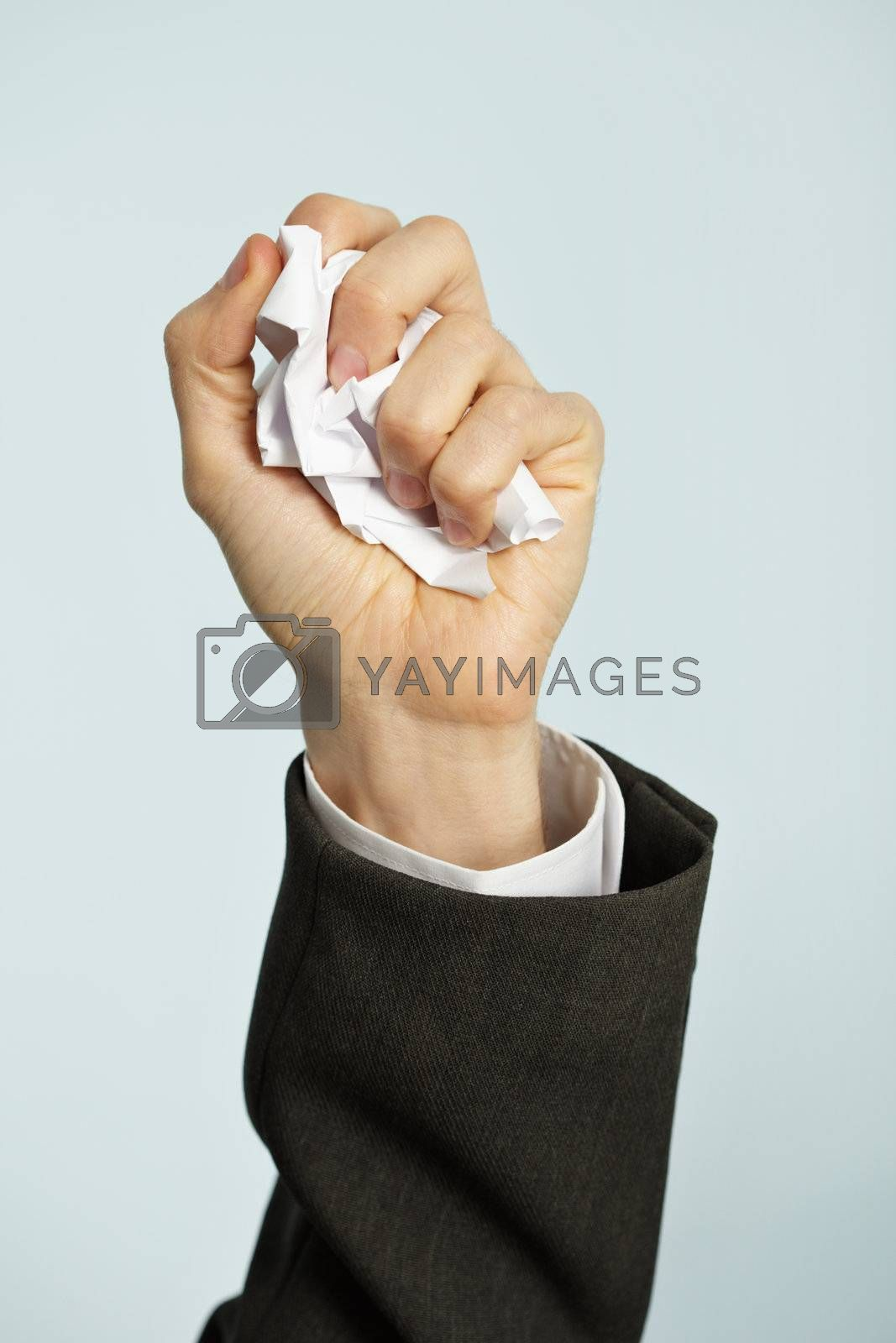 Royalty free image of Hand crumples paper - hated work by pzaxe