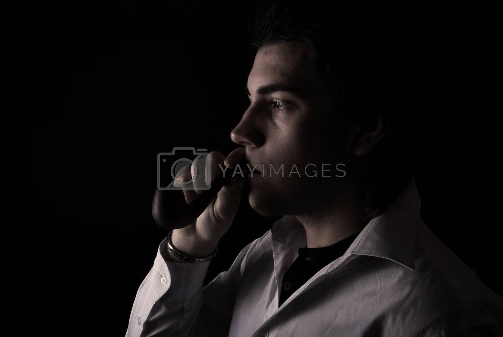 Royalty free image of portrait of a young man with pipe by HASLOO