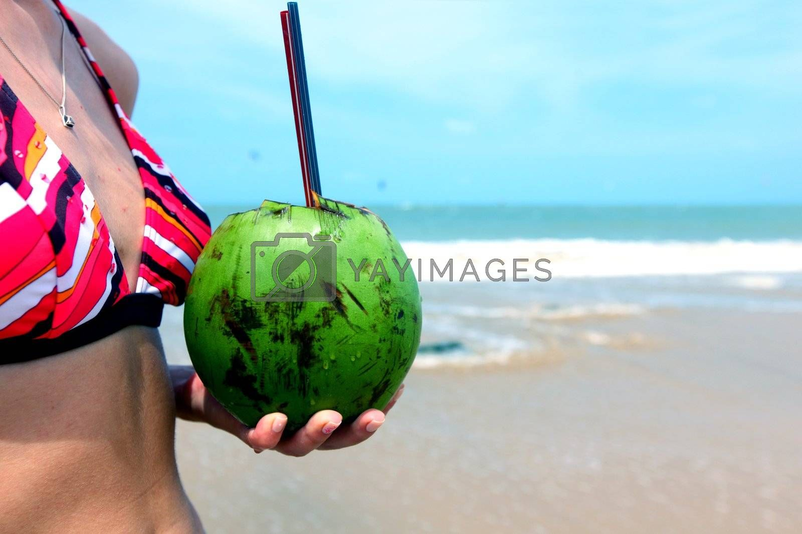 girl holding coconut cocktail in hands