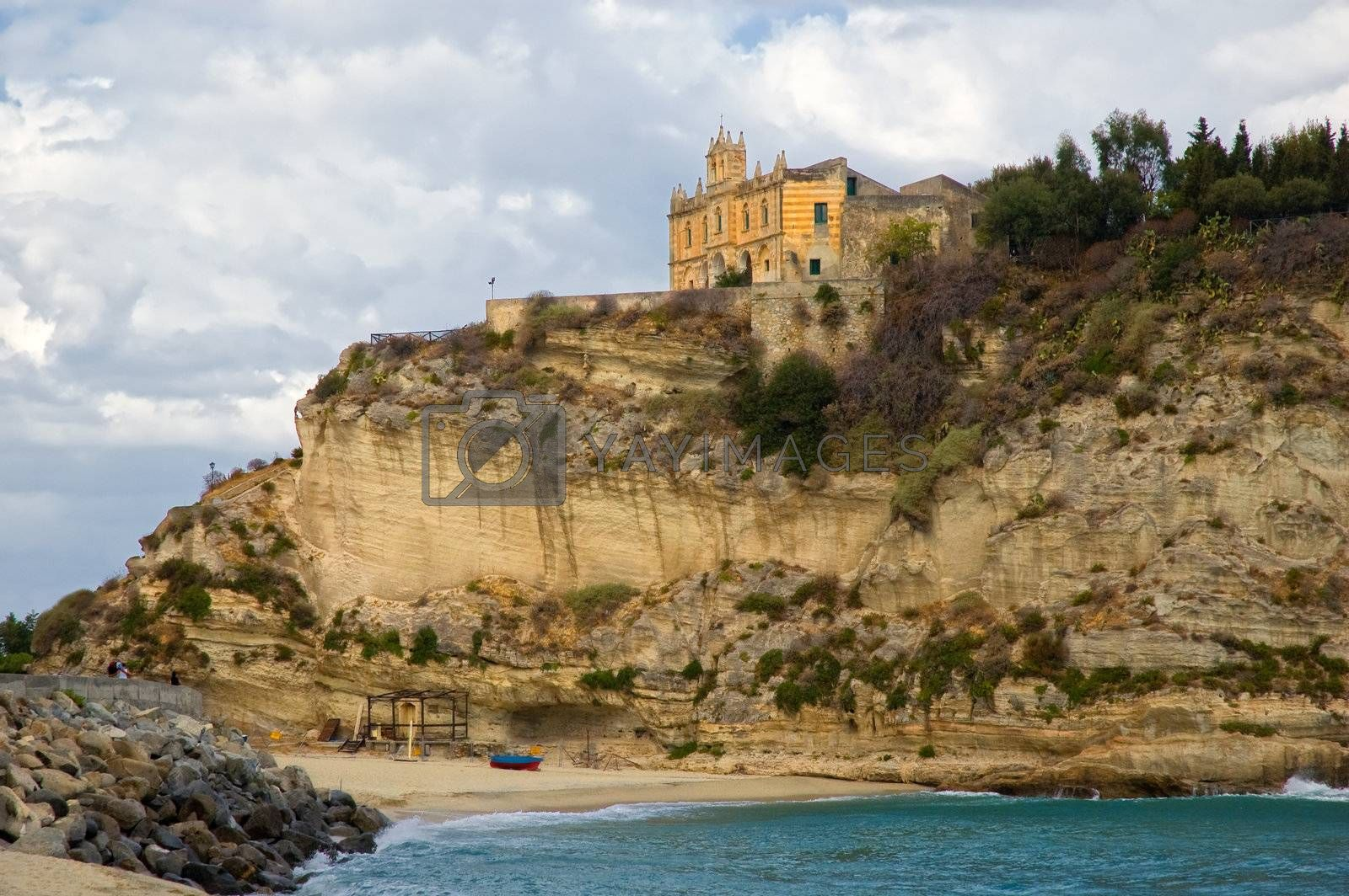 Shot taken in Tropea, Calabria, Italy. Church on rocks with sea and boat on beach.