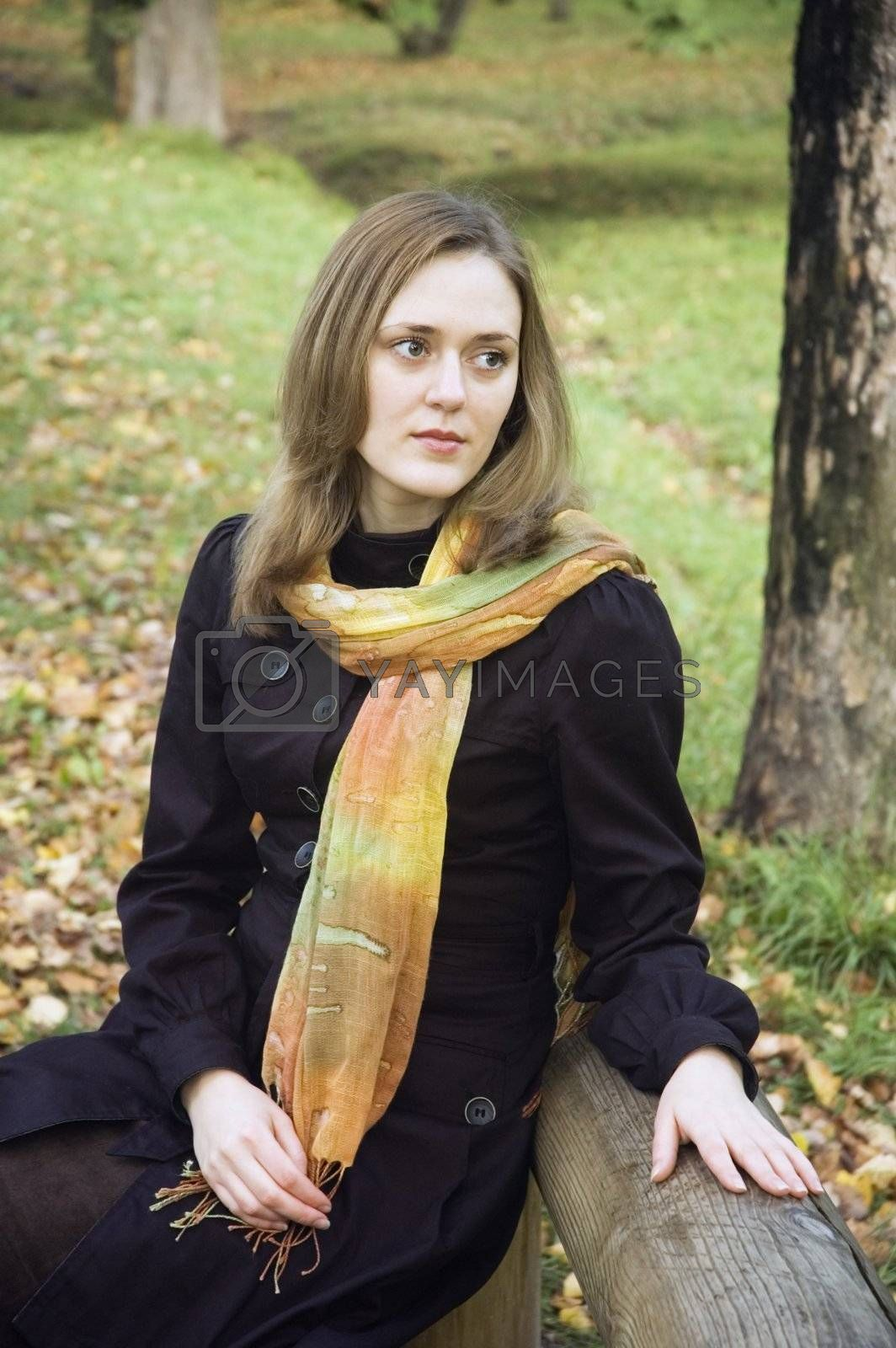 The young girl sits on a bench in park