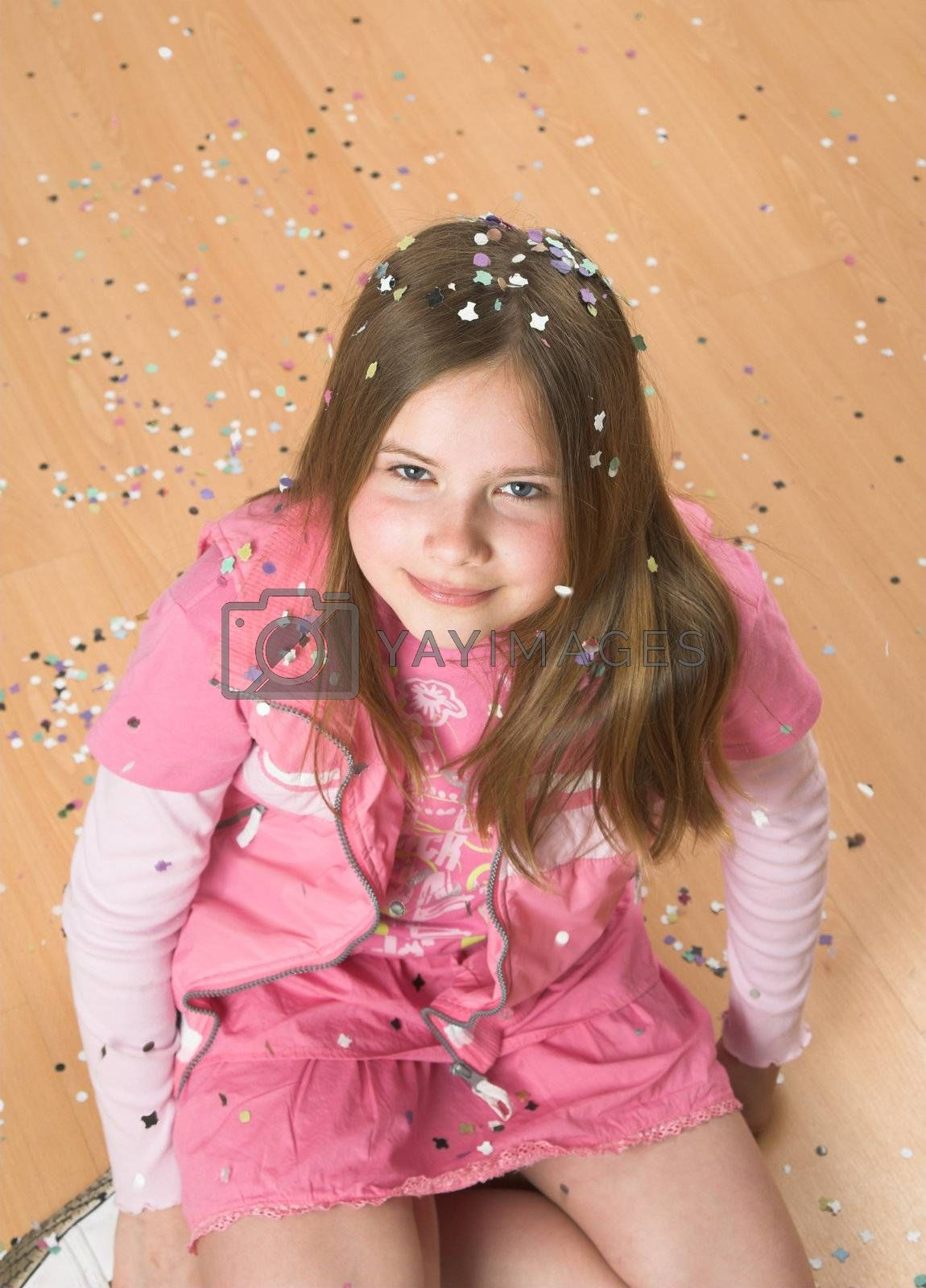 Little blond girl sitting on the floor covered in confetti