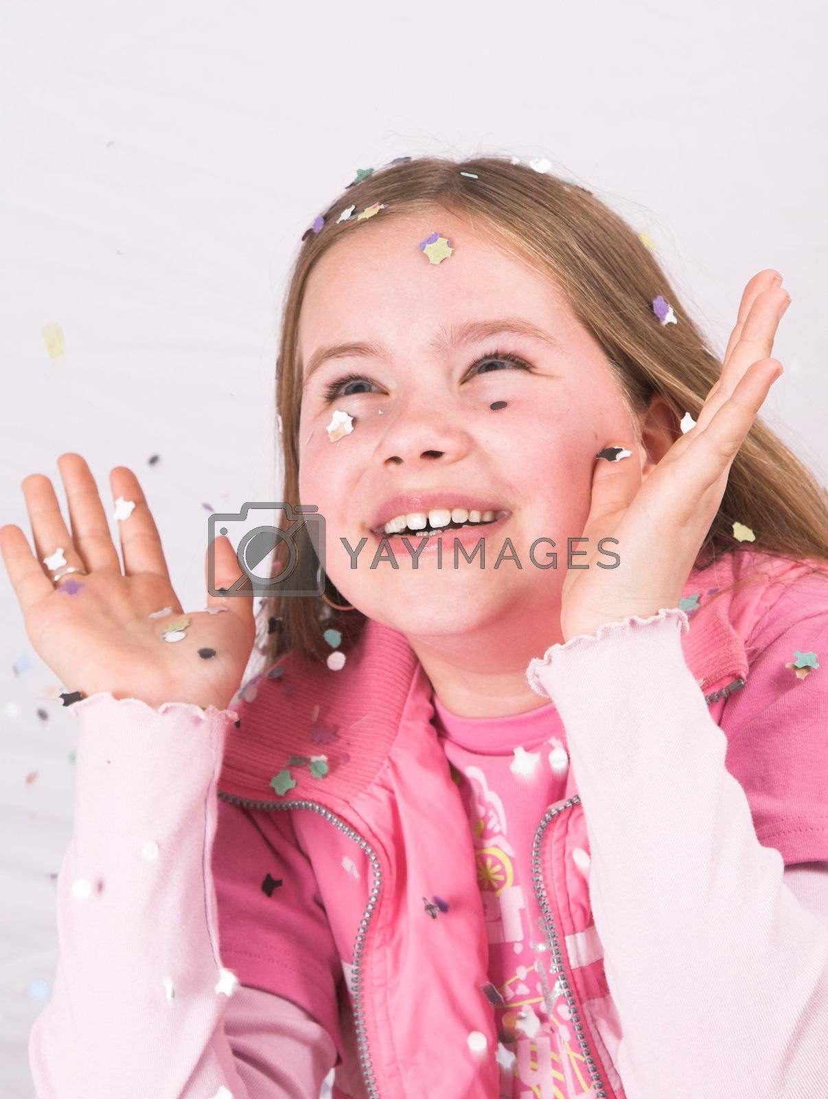 Pretty ten year old girl holding her hands up to catch the confetti coming down