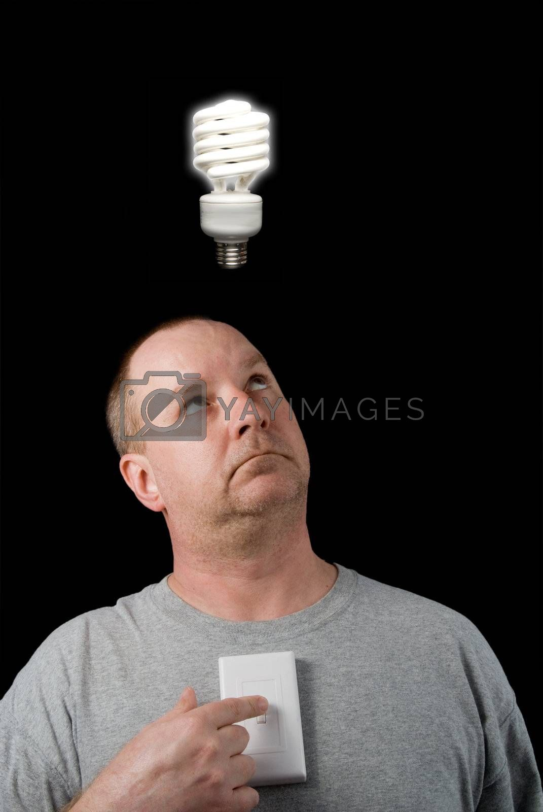 A man looking at a lighted lightbulb over his head.