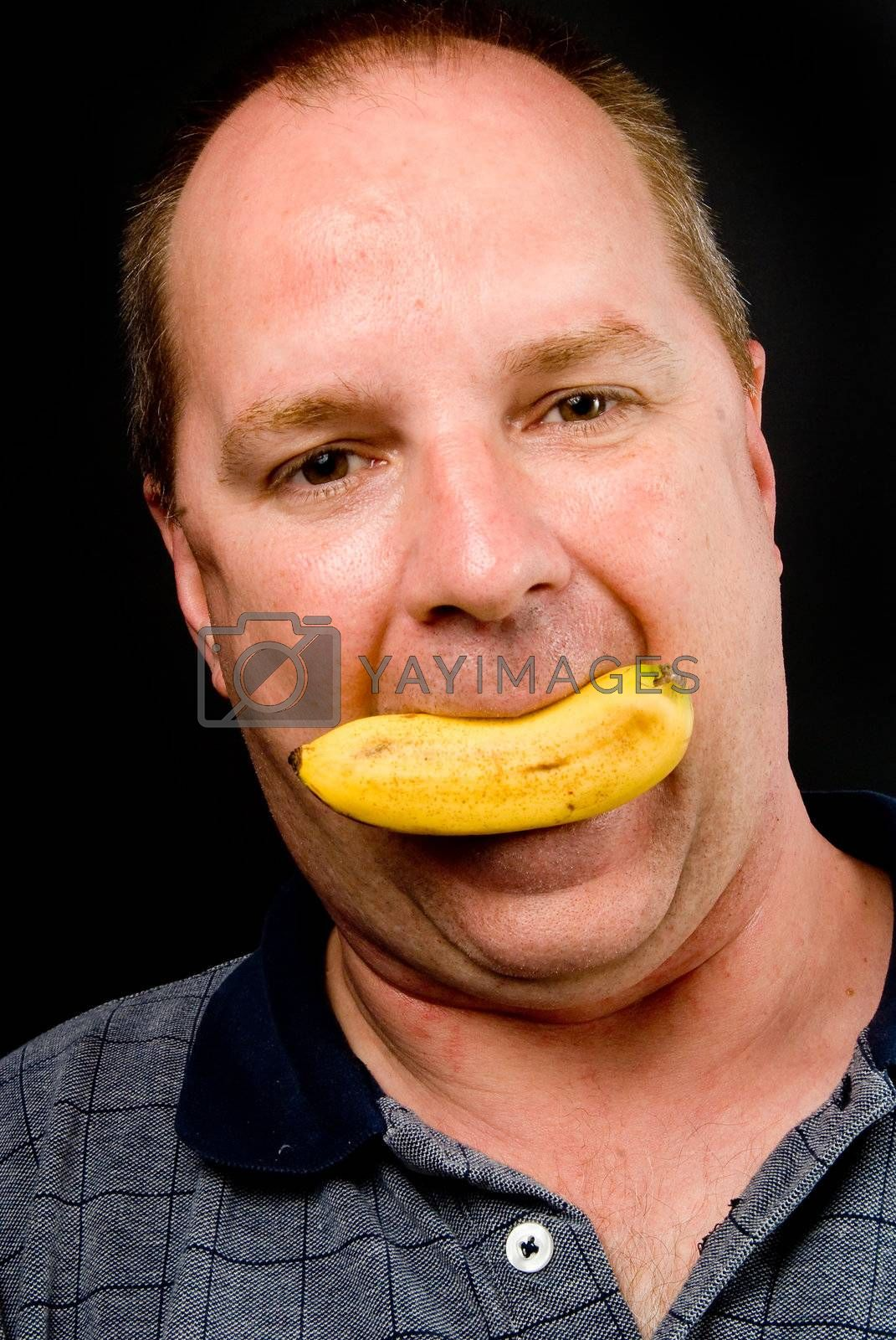A man smiling with a small banana in his mouth.
