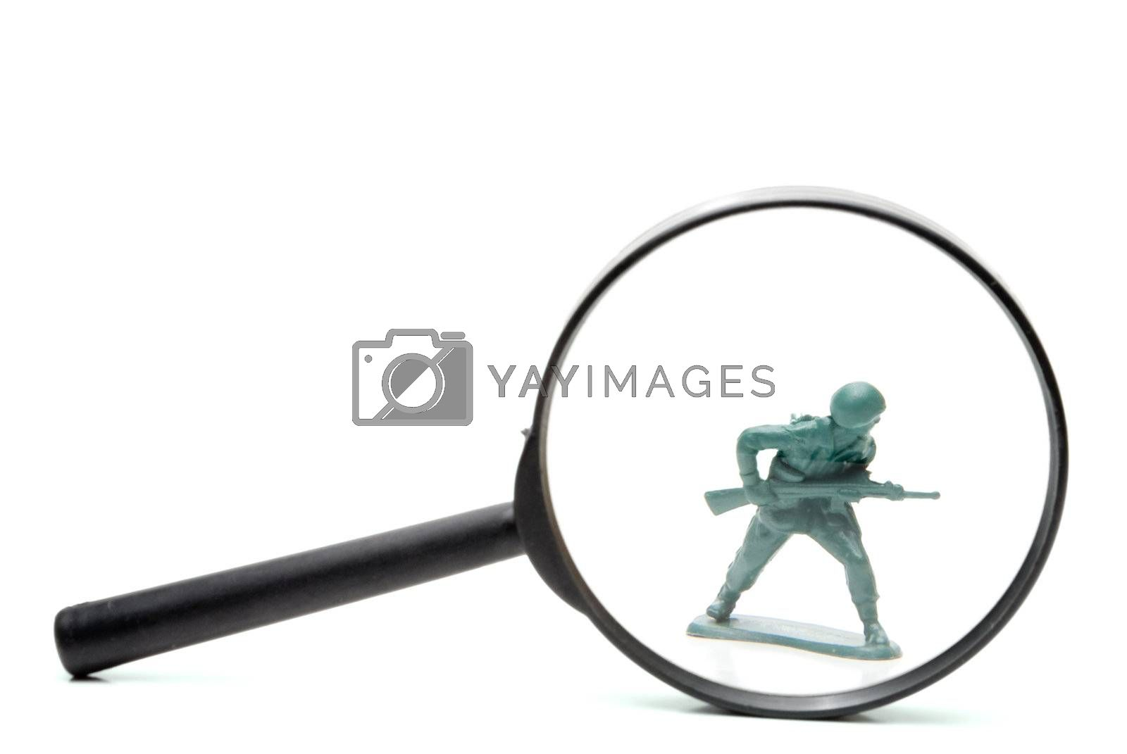 A toy soldier being investigated under a magnifying glass.