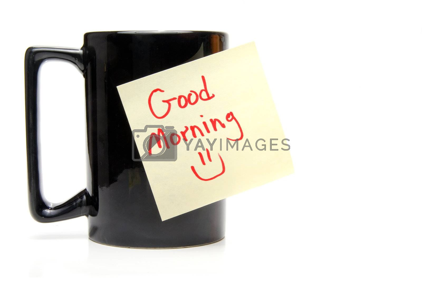 A coffee cup with a good morning sticky note.