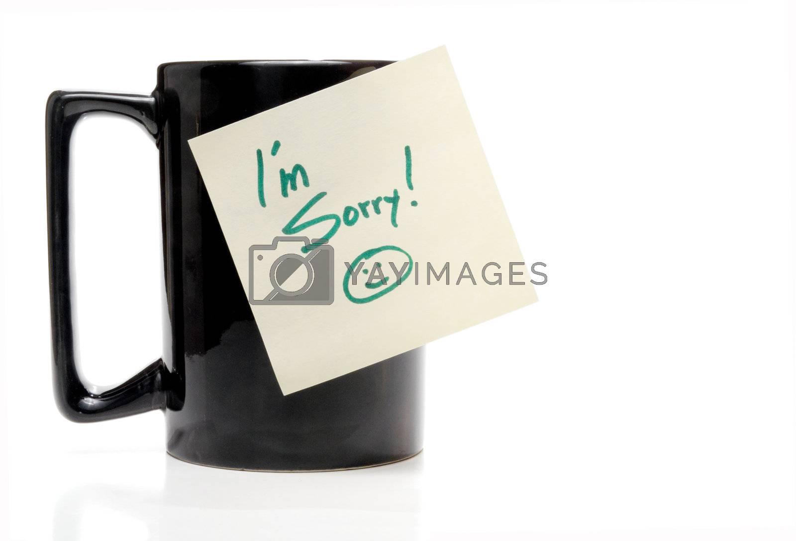 A coffee mug with an Im Sorry note.