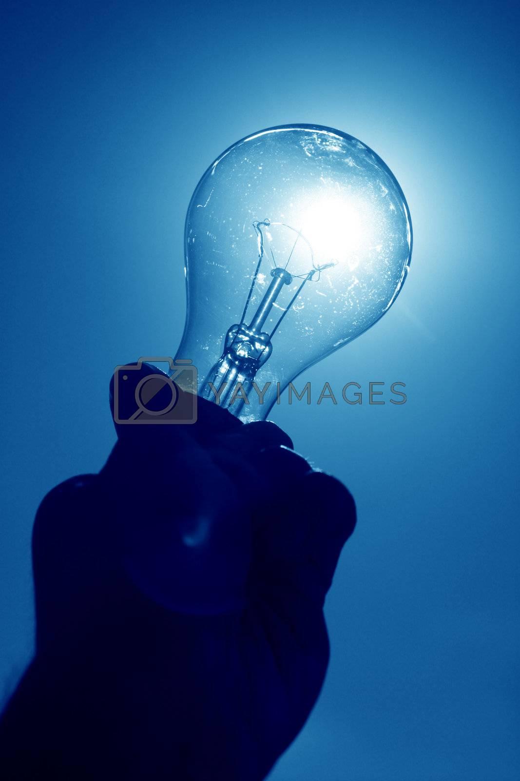 blue light bulb in man finger