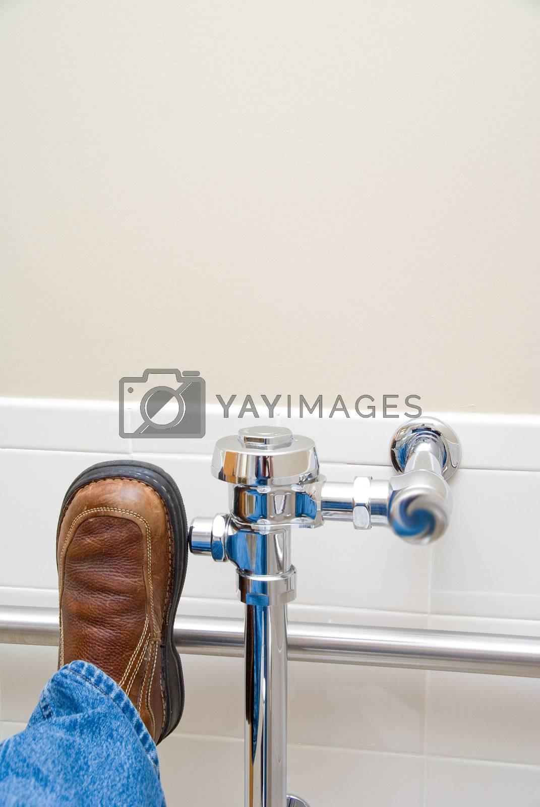 A persons shoe flushing a public toilet.