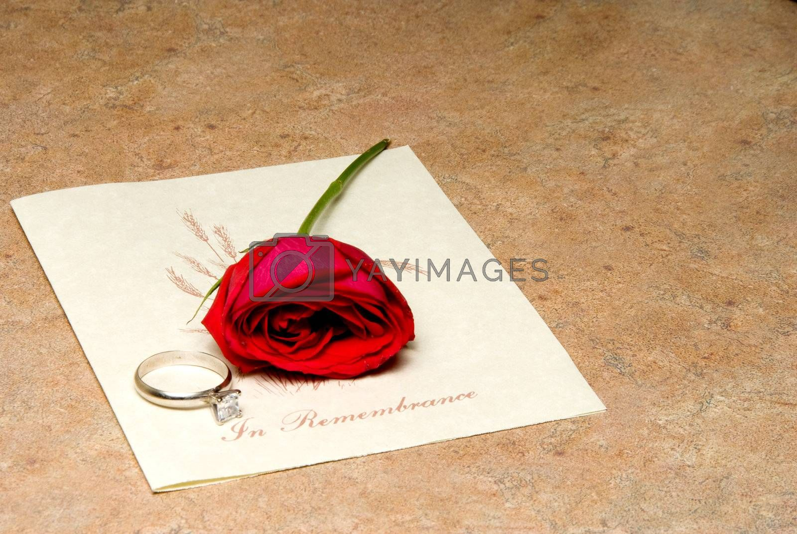 A funeral program with a rose and wedding ring.