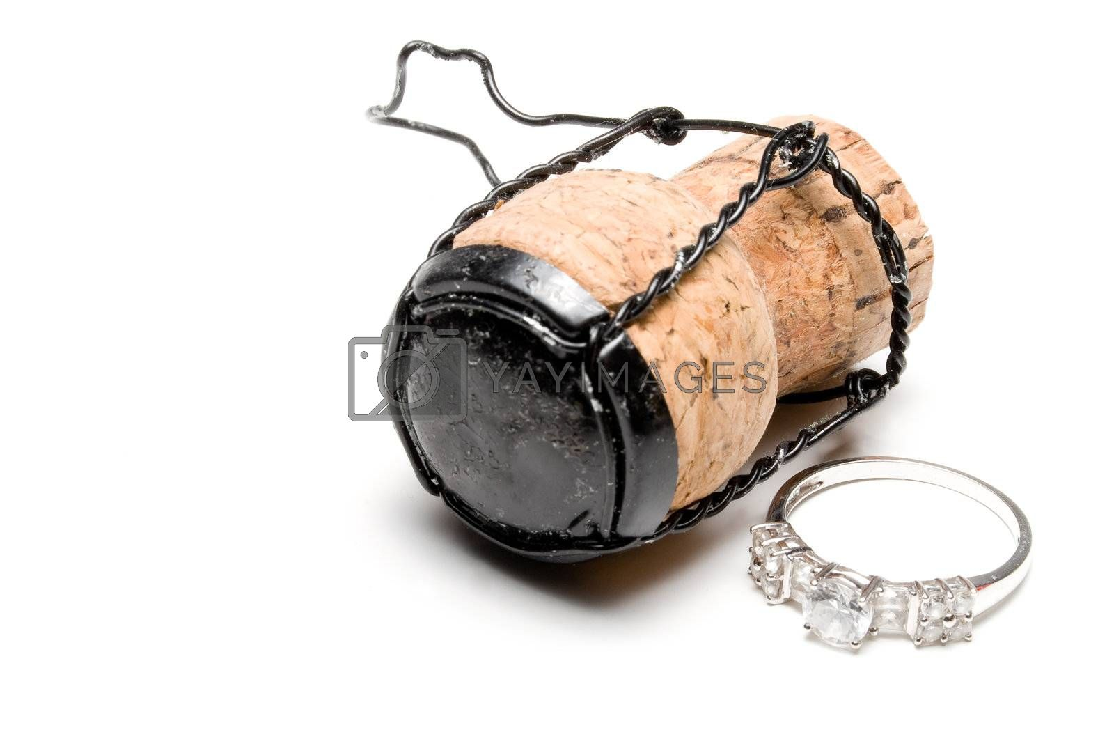 A wedding ring next to a champagne cork.