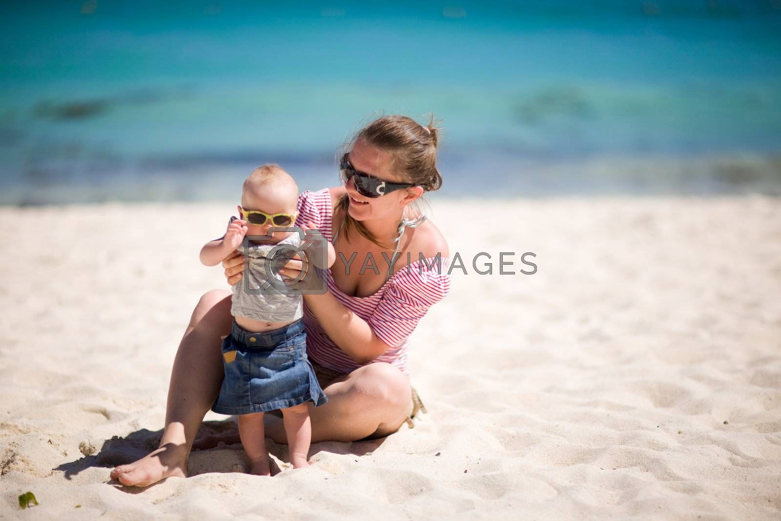 Young mother and baby girl in sunglasses on white sand tropical beach