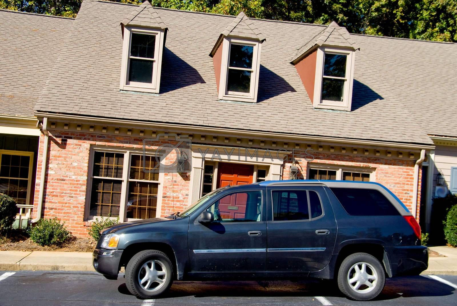 An SUV parked in fron of a leaning apartment building.
