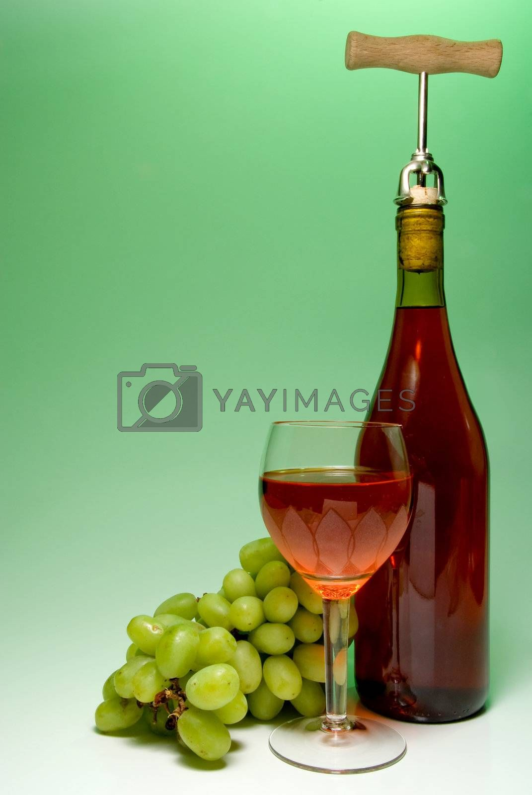 A glass of wine beside grapes and a bottle.