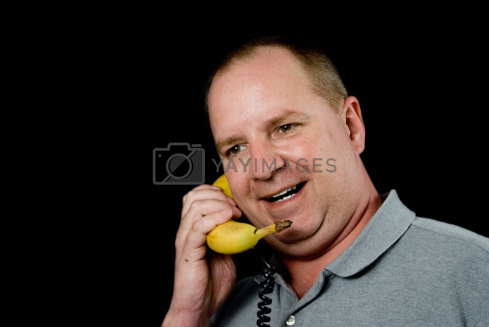 A man talking on a banana phone.