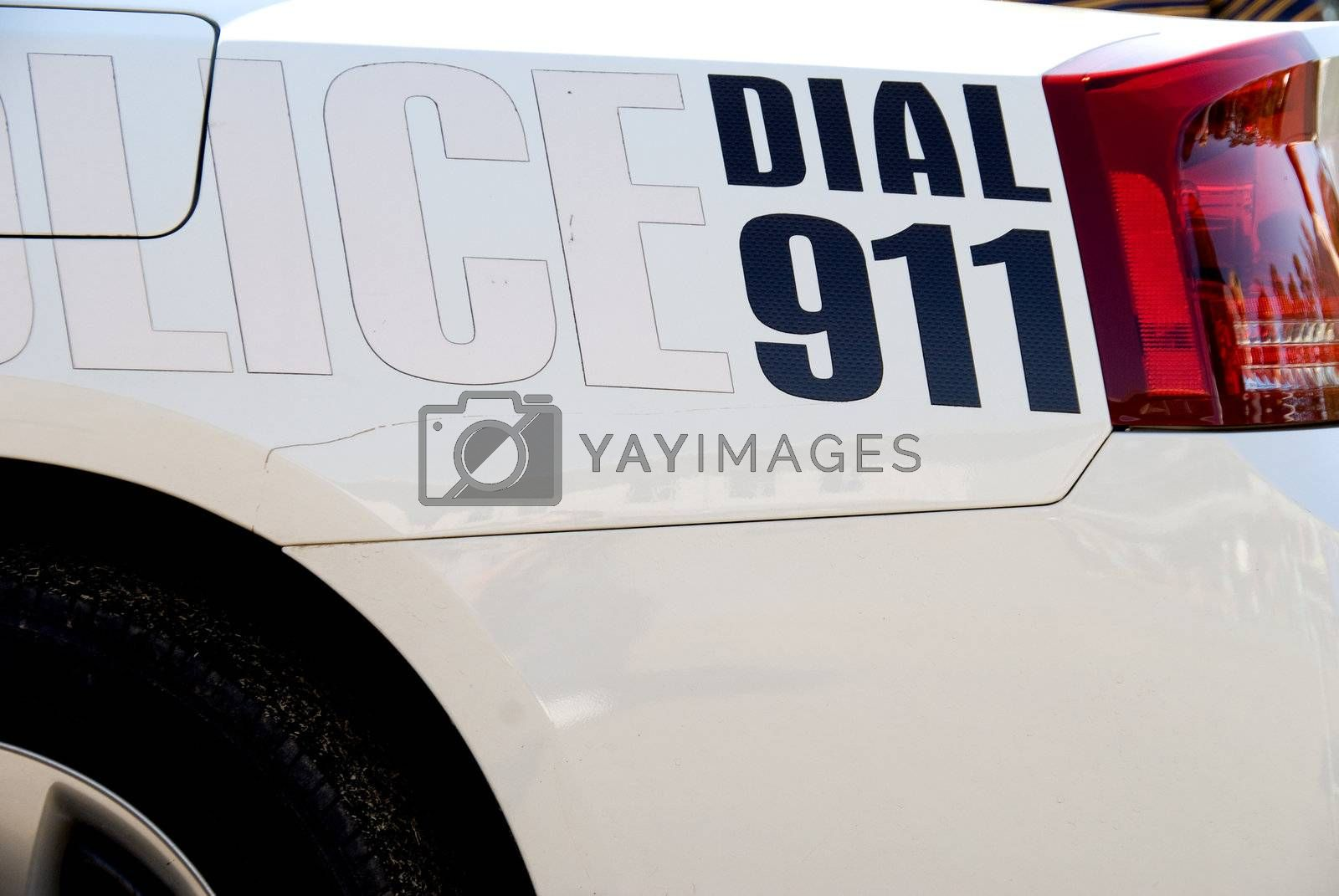 A message on the back of a police car: Dial 911.
