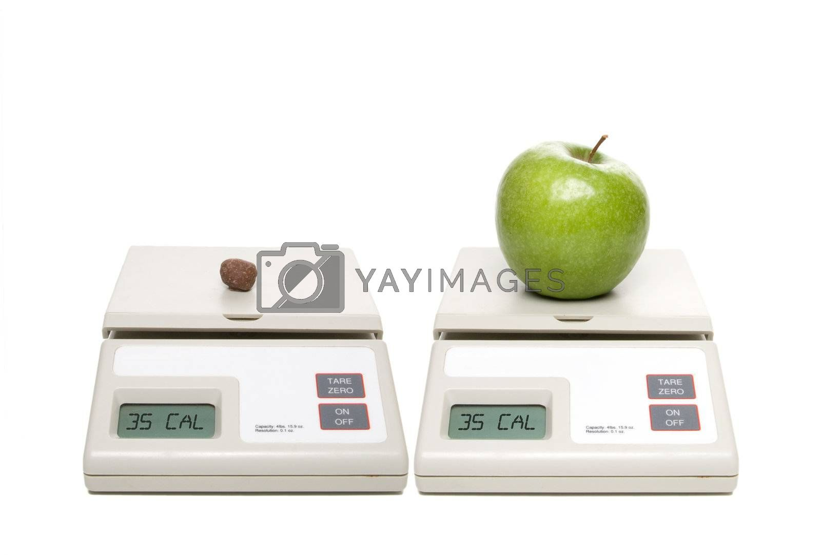 A scale with chocolate candy and one with an apple.
